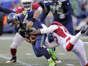 Seattle Seahawks quarterback Russell Wilson, left, is sacked by Arizona Cardinals' Chandler Jones, right, during the first half of an NFL football game, Sunday, Dec. 30, 2018, in Seattle.