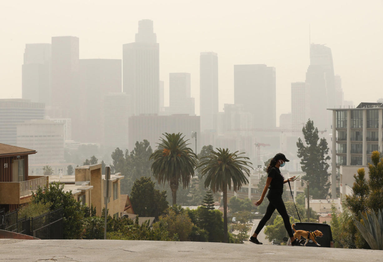 Breya Hodge walks her dog, Sophie, on Sept. 14 as smoke from the Bobcat Fire shrouds downtown Los Angeles.