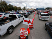 Motorists wait in line to enter a COVID-19 vaccination site at the University Mall parking garage in Tampa on Thursday, Feb. 11, 2021. The traffic was backed up for at least one mile onto Fowler Street.