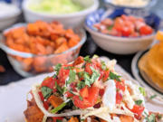 These vegetarian tostadas are stacked with two layers of smashed pinto beans, lettuce, pico and roasted sweet potatoes and bell peppers. Crumbled queso fresco and lime crema add the crowning touch.