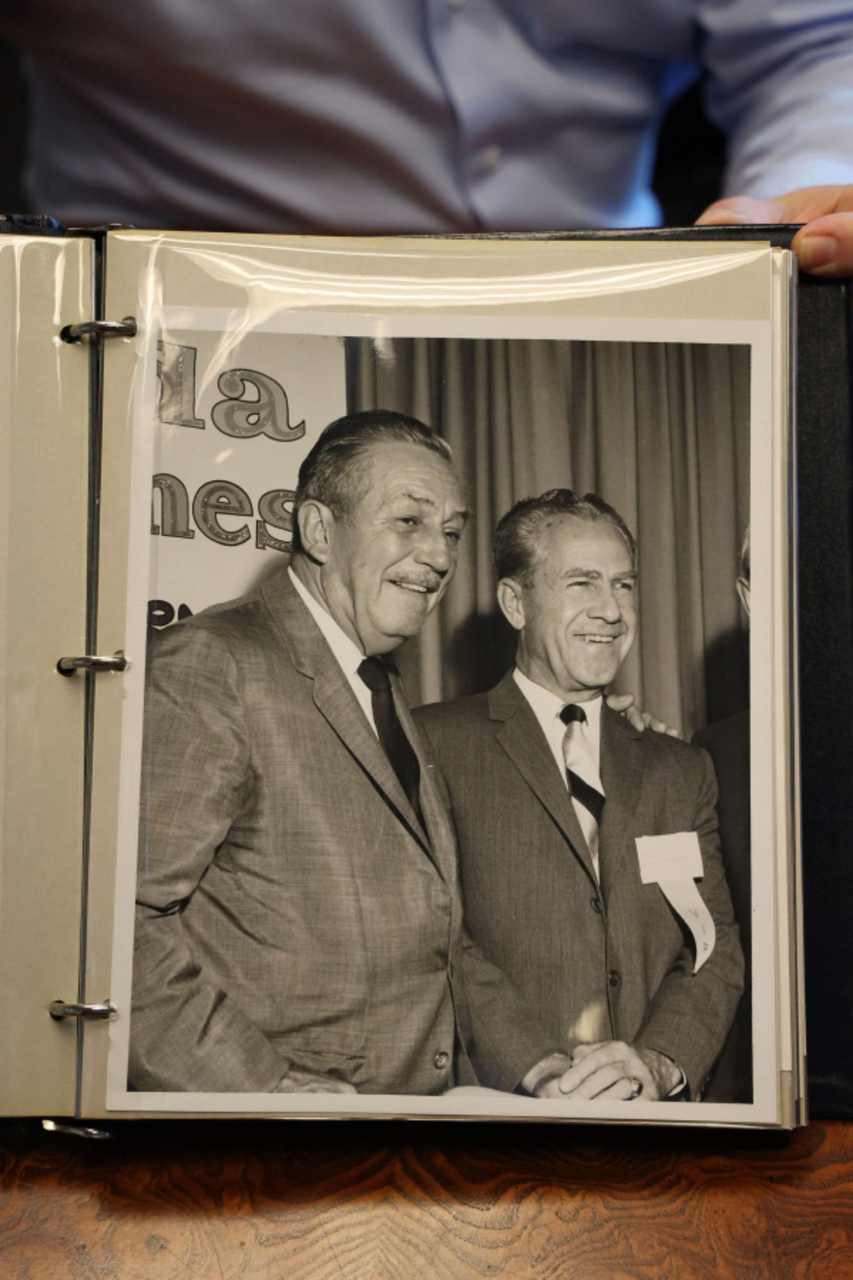 """Attorney Kent Hipp shows a photo of Walt Disney and Major General William """"Joe"""" Potter, from a photo album."""