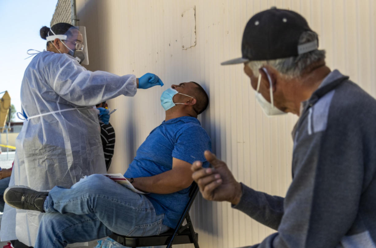 COACHELLA, CA - FEBRUARY 10, 2021: Medical assistant Trisha Edwards administers a Rapid COVID-19 test to farmworker Fernando Benitez of Thermal before getting the coronavirus vaccine at the Central Neighborhood Health Foundation on February 10, 2021 in Coachella, California. Fifty farmworkers are getting the vaccine here.