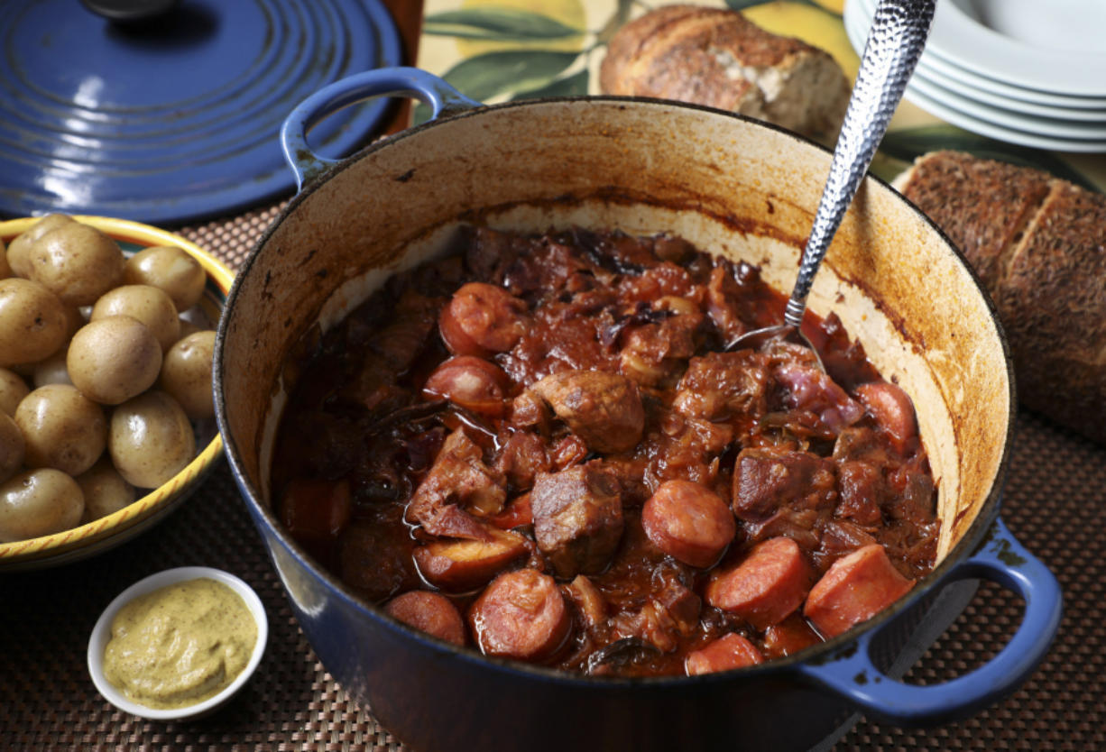 Pork simmers in a Dutch oven or slow cooker with cabbage and sauerkraut. Kielbasa is added near the end of cooking.