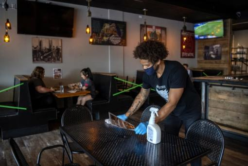 Bartender Britton Brown disinfects a table after customers leave Heathen Brewing in Vancouver in July.