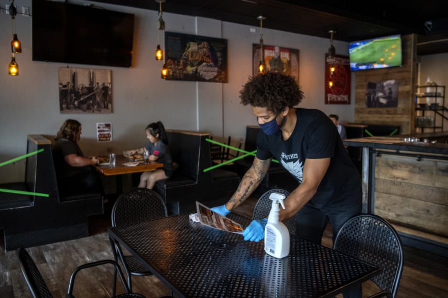 Bartender Britton Brown disinfects a table after customers leave Heathen Brewing in Vancouver  in July. Moving to Phase 2 will allow more Clark County restaurants to open indoor dining.