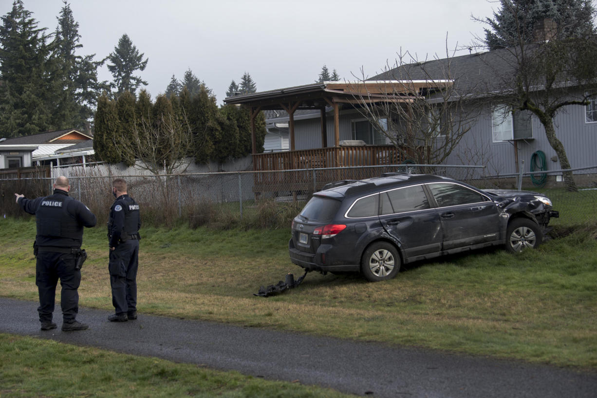 Police investigate at the scene after the vehicle came to a stop at Marrion School Park after crashing through a nearby garage Friday morning, Feb. 18, 2021.