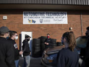 Automotive instructor Adam Eldridge, center in red mask, works with students as they prepare to push a car inside the auto shop at Cascadia Tech Academy. Remote learning has been a challenge for students learning hands-on occupations.
