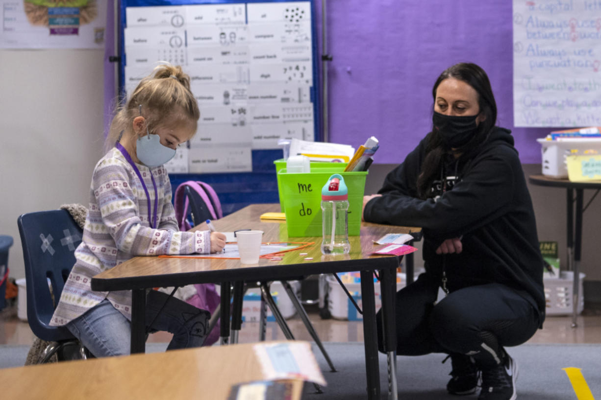 Kindergartner Knightley Wells does a math assignment while educational assistant Tiffany Shimmin observes last month at Captain Strong Primary School in Battle Ground.