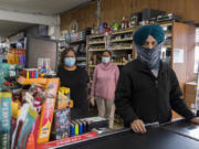 Priscilla Mosby of Amboy Market, from left, pauses for a portrait with Gurvinder Sarai, and her husband, Bharwinder Singh, the store's owner. Singh moved from India to America once he was an adult for better opportunity.