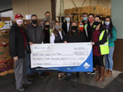 MINNEHAHA: Walk & Knock officials Tom Knappenberger and Adam Hegewald, left, present a check for $115,000 to the Clark County Food Bank.