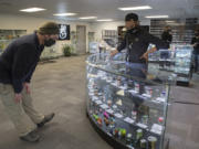 Damian Thomas of Vancouver, left, looks over the selection at the new Craft Cannabis location in northeast Vancouver while assisted by budtender Anthony Taylor during the shop's soft opening on Friday.