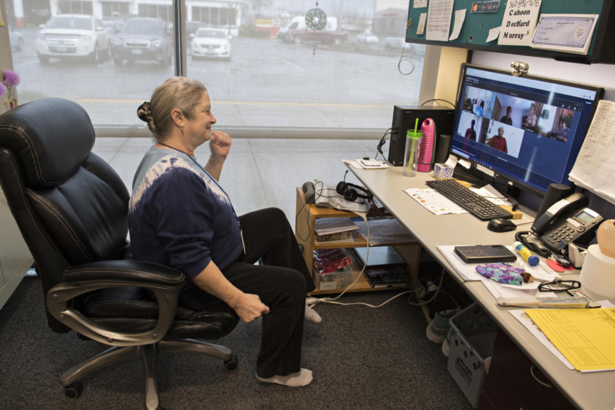 Laura Fitzgibbon, activities director for CDM Caregiving Services, joins clients in some exercises from her office chair via computer during a remote workout in Vancouver. Before the COVID-19 pandemic, Fitzgibbon saw clients in person, but now she has to see them virtually.