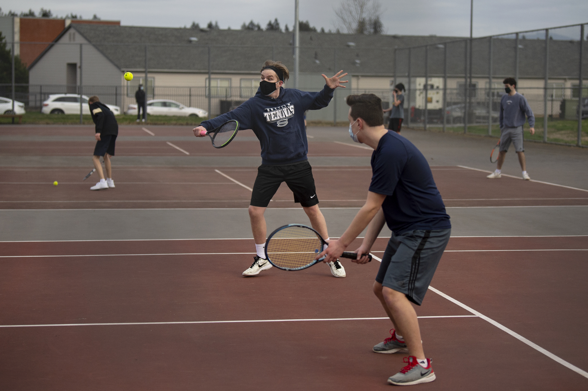 Skyview junior Noam Larson hits a return while teammate Ryan Oehler, a senior, watches on in a 3A/4A Greater St. Helens League boys tennis match on Monday, February 8, 2021, at Union High School. Monday was the first time in 333 days that high school sports held competitions.