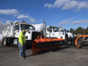 LEADOPTION Richard Harris of the Clark County Public Works Department walks past trucks used for plowing and deicing streets as crews get ready for the possibility of snow accumulation Wednesday afternoon, Feb. 10, 2021.