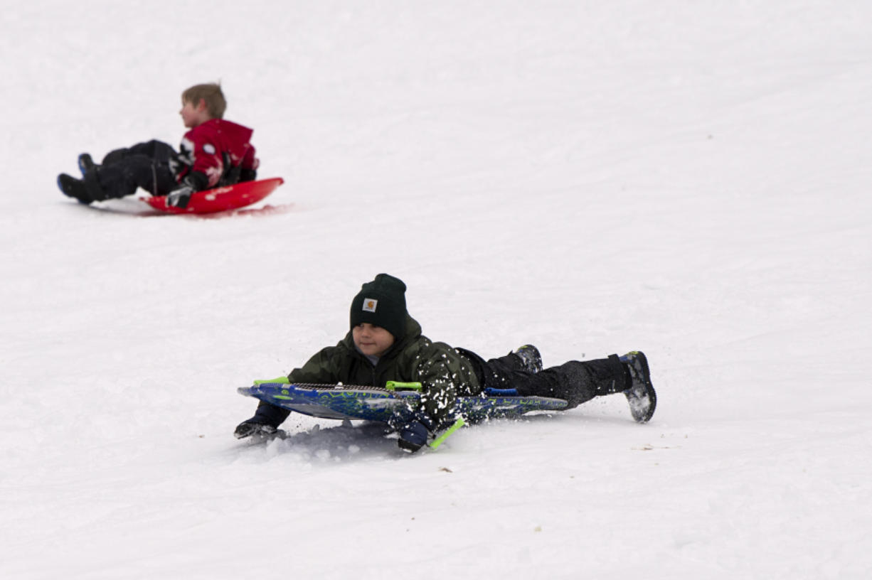 Madden Dreier, 6, slides headfirst on Saturday morning while playing in the snow at Sorenson Park in Felida.