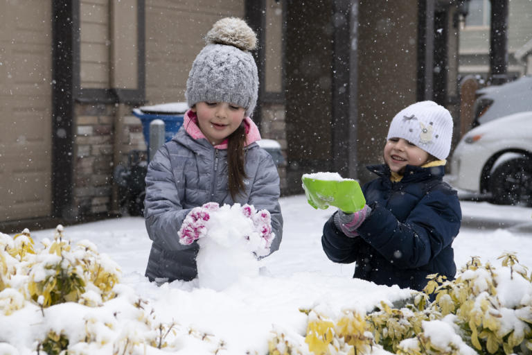 Emilya, 6, and Katerina, 5, play in the snow on Friday, February 12, in front of their home in the Minnehaha neighborhood. Snow continued to accumulate Friday morning as the winter storm persisted.