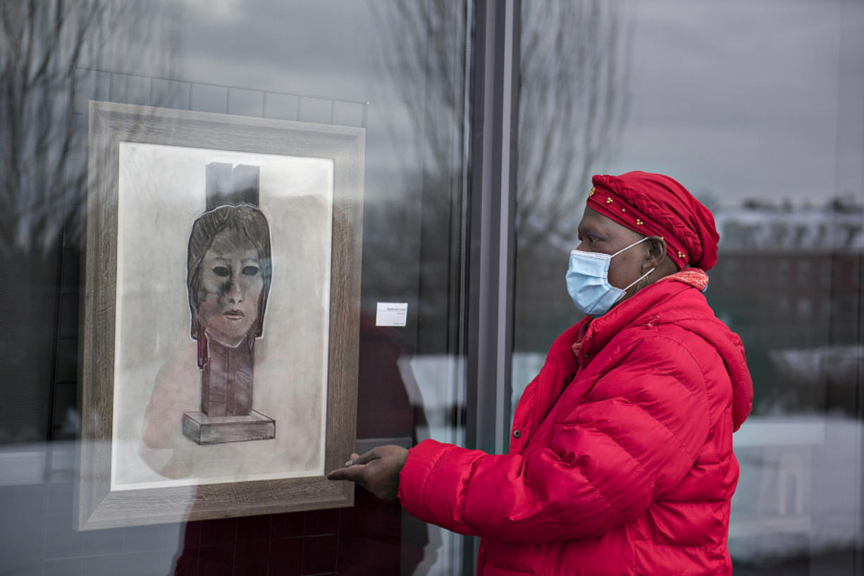 "Artist Claudia Carter looks over a piece titled, ""Self Portrait,"" in the side window exhibit at Vancouver Community Library in Vancouver. Carter has been putting on a Black History Month installation for four years. In February 2020, she was diagnosed with cancer and her goal was to live until at least February 2021 for one last installation."