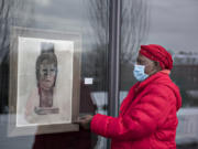 """Artist Claudia Carter looks over a piece titled, """"Self Portrait,"""" in the side window exhibit at Vancouver Community Library in Vancouver. Carter has been putting on a Black History Month installation for four years. In February 2020, she was diagnosed with cancer and her goal was to live until at least February 2021 for one last installation."""