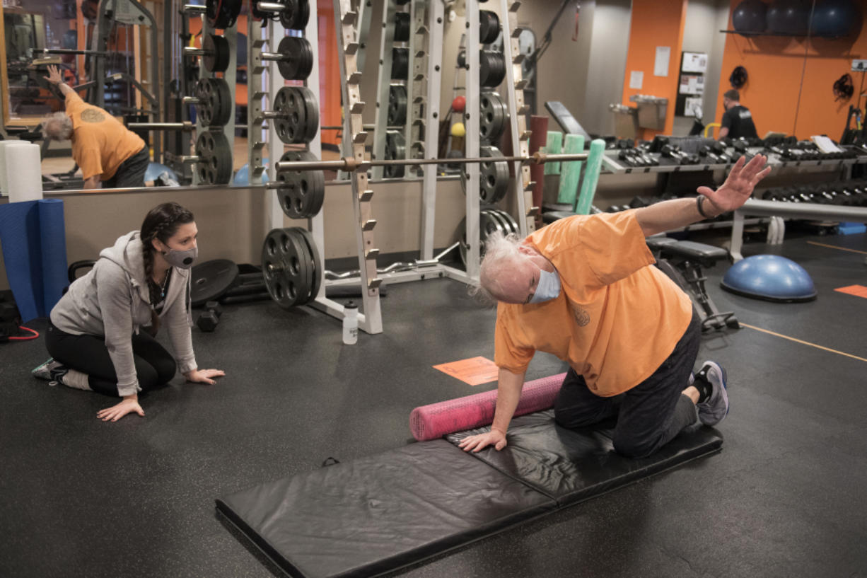Alicia Rose, left, personal trainer and group fitness instructor at Northwest Personal Training, works with Cliff Miller of Vancouver in downtown Vancouver. Gyms are now open for 25 percent capacity for in-person training.