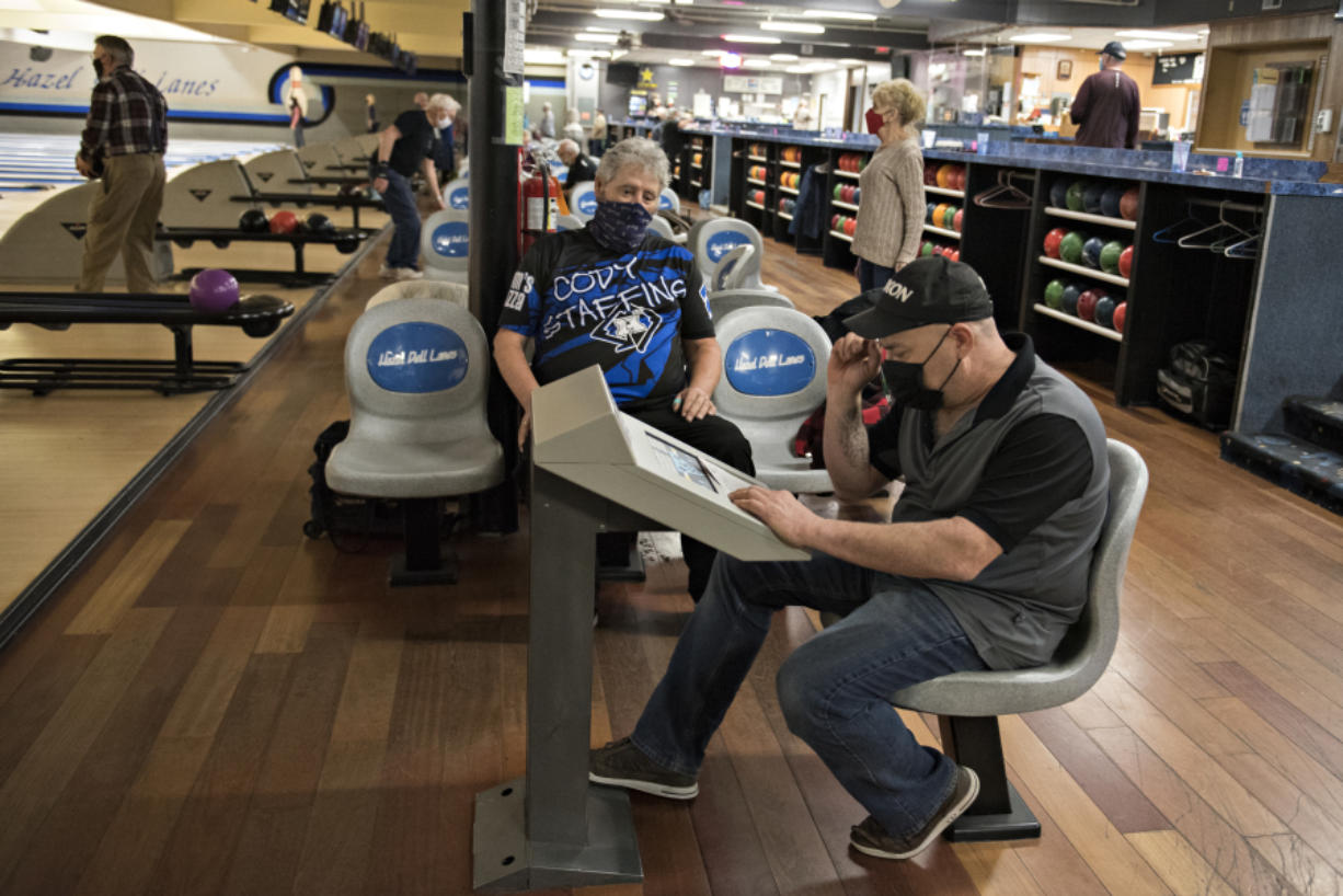 Rick Enge of Camas, in blue and black, joins Robert Black of Vancouver, right, as they keep track of the score at Hazel Dell Lanes on Wednesday. Hazel Dell Lanes reopened this week following the end of a three-month period of increased business restrictions prompted by a rise in COVID-19 cases.