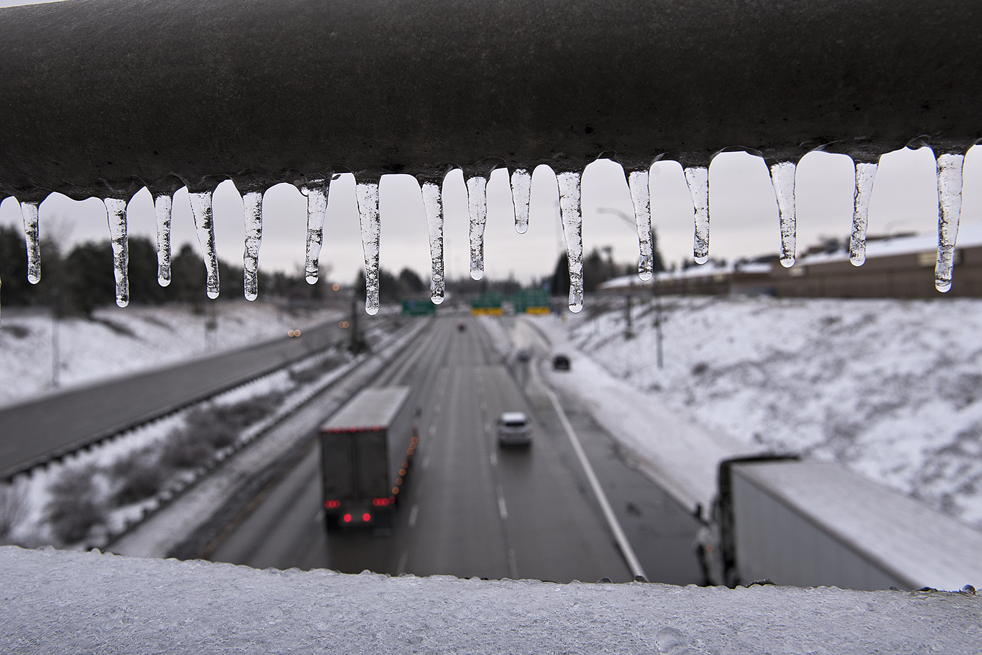Icicles hang from the railing of a bridge as sporadic traffic flows smoothly in the northbound lane of Interstate 205 following an ice storm Monday morning, Feb. 15, 2021. (Amanda Cowan/The Columbian)