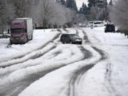 Motorists navigate roads with sketchy winter conditions including snow and ice Monday morning, Feb. 15, 2021.