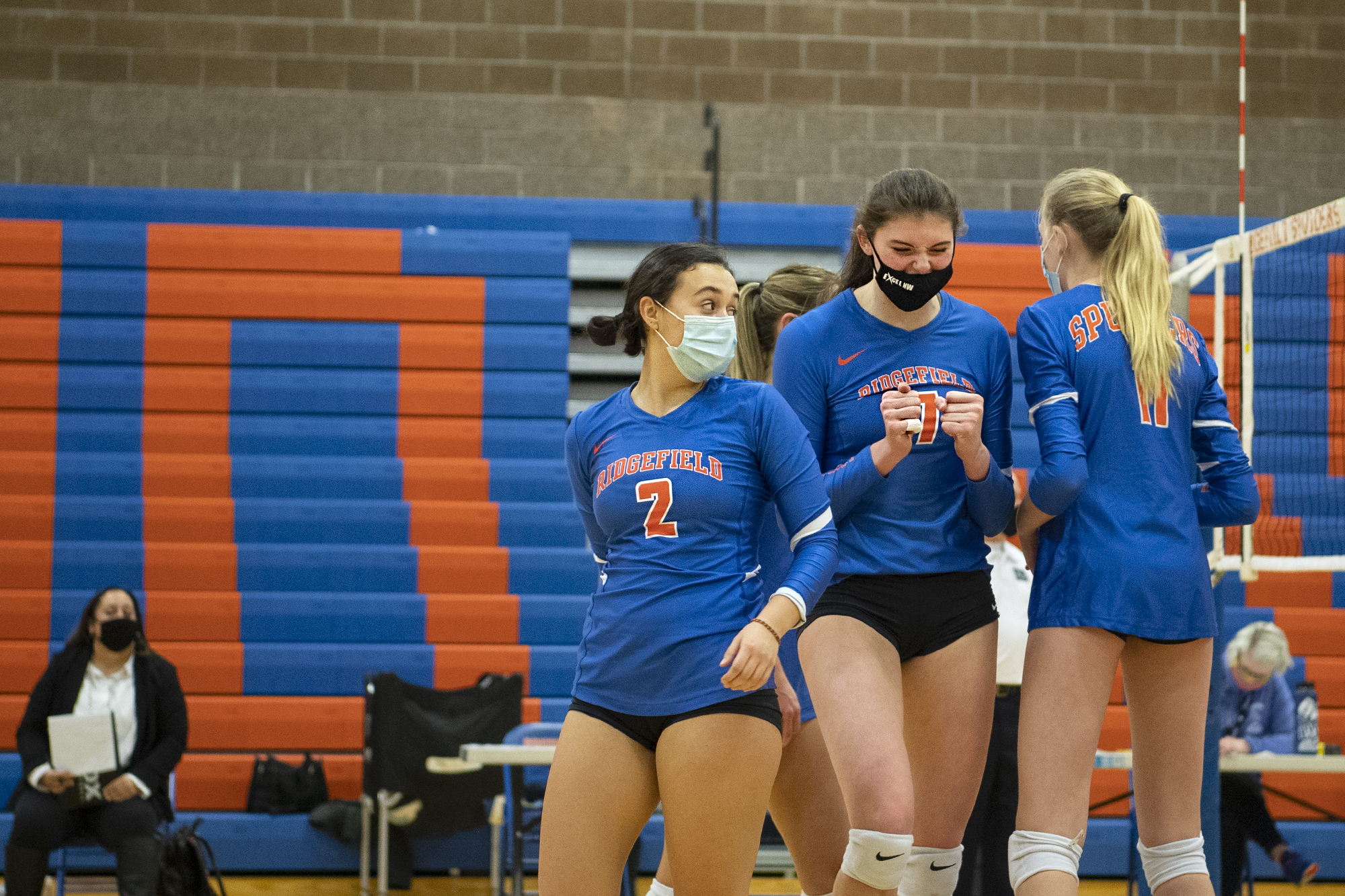 Ridgefield's Kohana Fukuchi, left, looks back toward Ali Andrew, center, who shows frustration over reading a lob hit wrong on Tuesday, February 16, 2021, at Ridgefield High School. Ridgefield won 25-20, 25-9, 25-12 over Mark Morris in its first volleyball match since winning the 2A State Championship in fall 2019.
