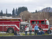 Fans watch from behind a perimeter fence during Saturday's game between Columbia River and Woodland. The game at Woodland High School was played with limited crowd capacity because of COVID-19 restrictions.