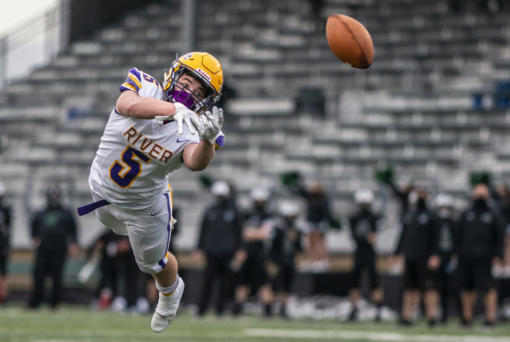 Columbia River's Max Sturtevant tried to make this catch at Woodland High School on Saturday. If he had, only players, coaches, game officials and a few dozen fans in the bleachers would have seen it in person. (Nathan Howard/ For The Columbian)
