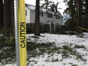 Caution tape surrounds downed branches in front of a house along West 32nd Street in Vancouver on Feb.
