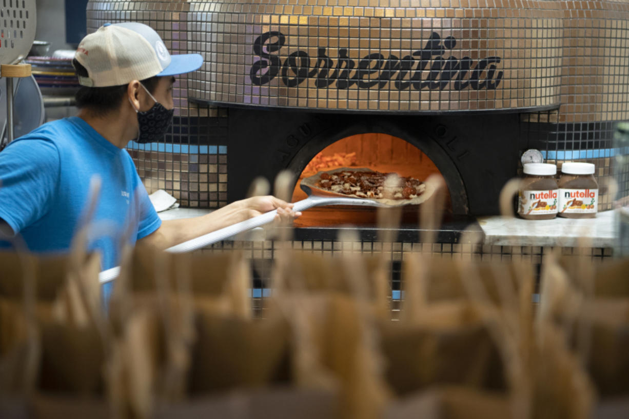 Antonio Fernandez pulls a pizza out of the wood-fired oven at Pizzeria La Sorrentina on Thursday. Support a Senior, Rescue a Restaurant started in January with a donation from Giving Group Realty in Vancouver to the nonprofit Northwest Wine & Food Society, which in turn purchased gift cards from small local restaurants.