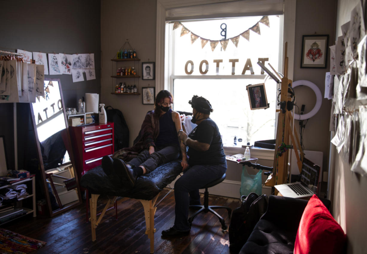 """Jainai Jeffries, owner of fyd mi ink, right, works with a client Audra Bergstrom, left, at the tattoo boutique in Vancouver. Jeffries is also an illustrator, concept designer and comic artist. """"It wasn't until seventh grade when I was playing Final Fantasy 7, when I looked in the back of the book and I saw the term 'character designer,'"""" Jeffries said. """"I said 'That's what I want to do.' I didn't get really serious about it until I was in Japan for a year in an exchange program with my college."""