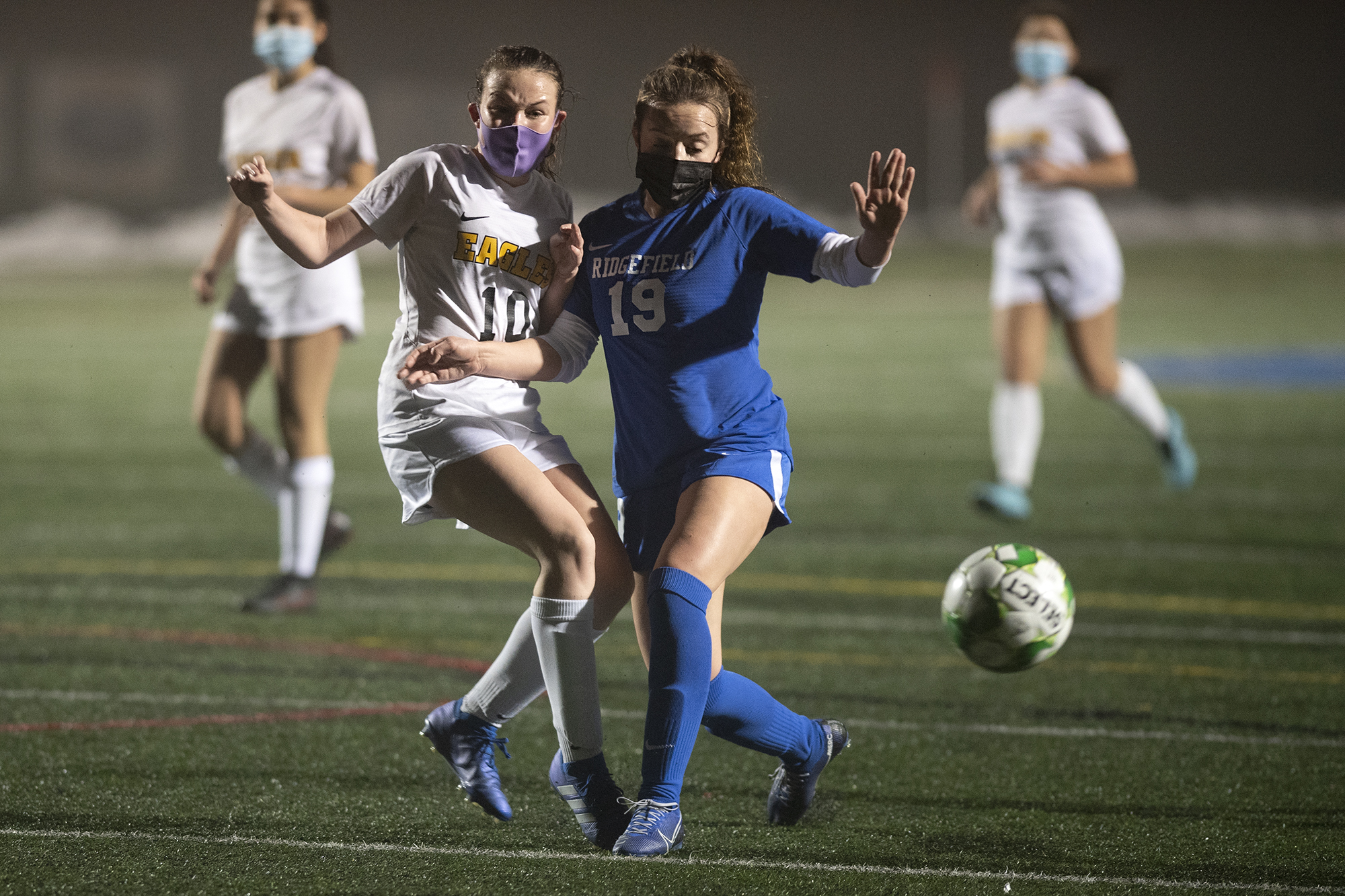 Hudson's Bay's Liza Perkins clears the ball from attacking Ridgefield forward Paytn Barnette in a 2A Greater St. Helens League girls soccer match on Thursday, February 18, at Ridgefield High School. The Spudders won 5-0. (Joshua Hart/The Columbian)