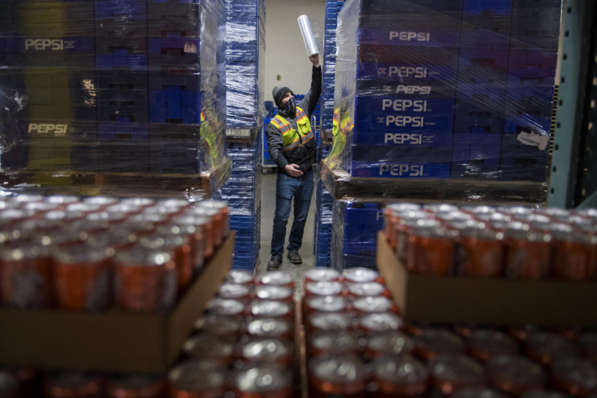 Keith Bunn prepares empty containers for beverage refills at Corwin Distributing in Ridgefield. Corwin Distributing Co. expects to suffer if a new tax on sweetened beverages, introduced in a Washington Senate committee meeting this week, is passed into law.