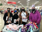 VAN MALL: TMG employees Michelle Villarma, Megan Francis, Elizabeth Divers and Vanessa MacAllister shopped for holiday gifts for foster children sponsored by TMG Cares.