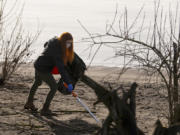Volunteer Raechal Burke reaches to pick up a piece of trash on Saturday at Marine Park. Vancouver's Water Resources Education Center hosted eight masked volunteers in a spring cleanup of the park and its beach.