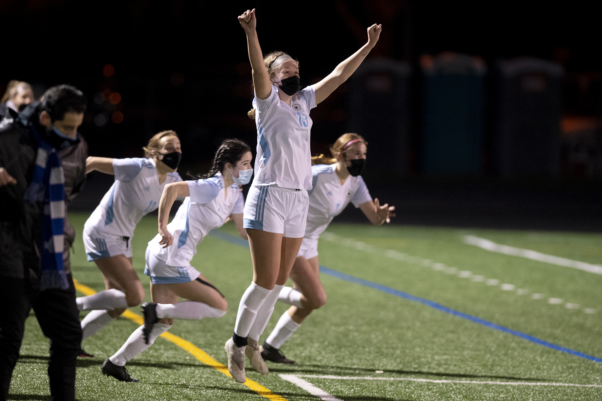 Hockinson's Grace Abbott raises her arms in celebration as teammates run on the field in victory on Saturday, February 27, 2021, at Columbia River High School. The Hawks earned a 1-0 victory over Columbia River in a rematch of the 2019 2A State girls soccer championship.
