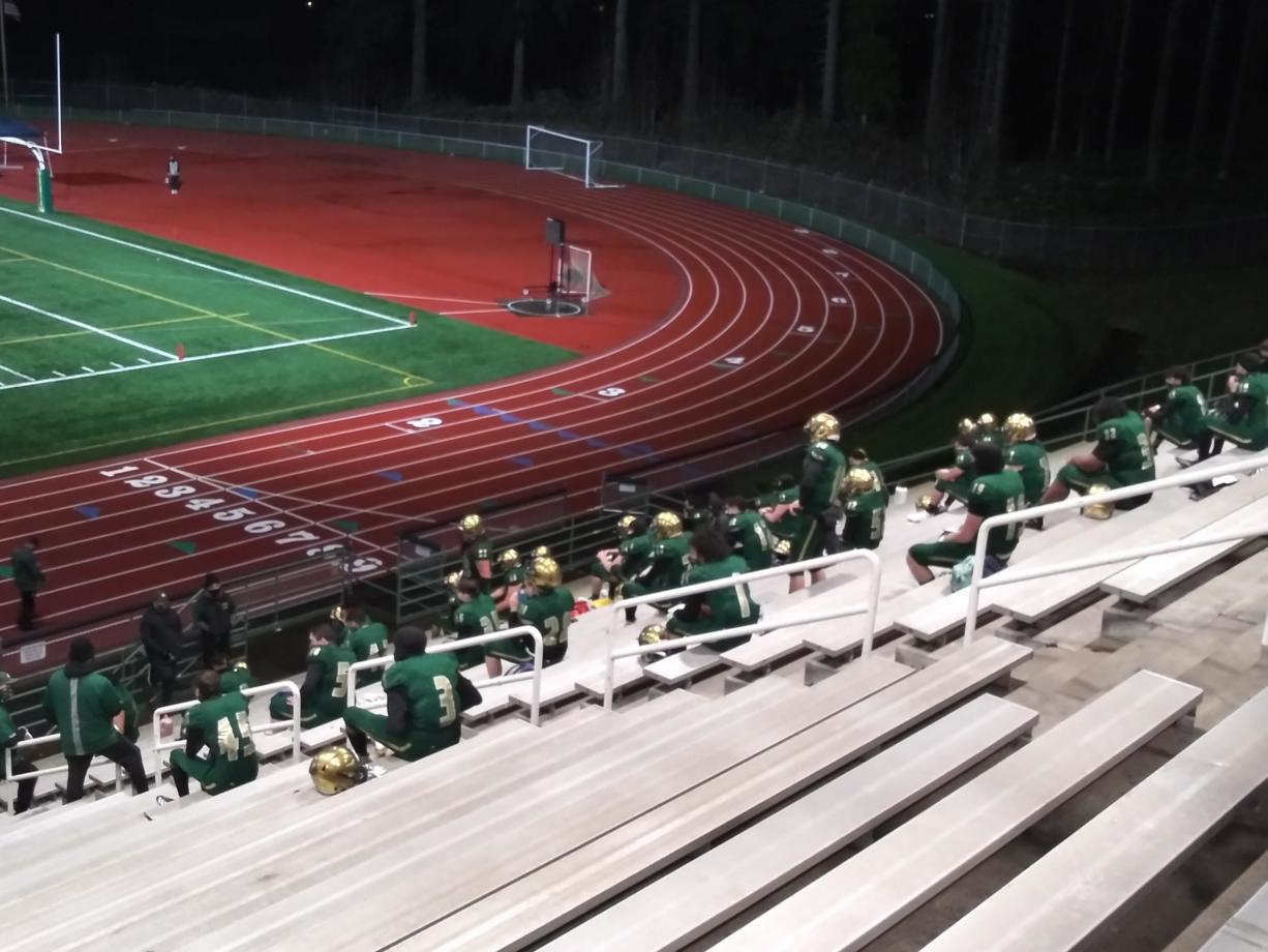 Evergreen football players receive pre-game instruction at their makeshift locker room in the empty stands at McKenzie Stadium (Tim Martinez/The Columbian)