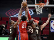 Philadelphia 76ers center Joel Embiid (21) goes after a rebound with Portland Trail Blazers guard Rodney Hood, left, forward Robert Covington, center, and center Enes Kanter, right, during the first half of an NBA basketball game in Portland, Ore., Thursday, Feb. 11, 2021.