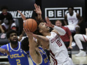 Washington State guard Isaac Bonton, right, shoots while pressured by UCLA guard Jules Bernard during the second half of an NCAA college basketball game in Pullman, Wash., Thursday, Feb. 11, 2021. Washington State won 81-73.