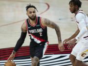 Portland Trail Blazers guard Gary Trent Jr., left, works around Cleveland Cavaliers guard Darius Garland during the second half of an NBA basketball game in Portland, Ore., Friday, Feb. 12, 2021.
