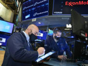 In this photo provided by the New York Stock Exchange, trader Fred DeMarco, left, works on the trading floor, Tuesday, Feb. 16, 2021. Stocks were modestly higher in morning trading Tuesday, pushed by energy companies who have seen record electricity prices due to the frigid cold impacting much of the country.