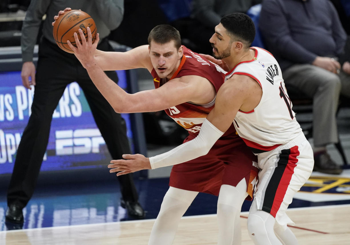 Denver Nuggets center Nikola Jokic, left, is defended by Portland Trail Blazers center Enes Kanter during the second half of an NBA basketball game on Tuesday, Feb. 23, 2021, in Denver.