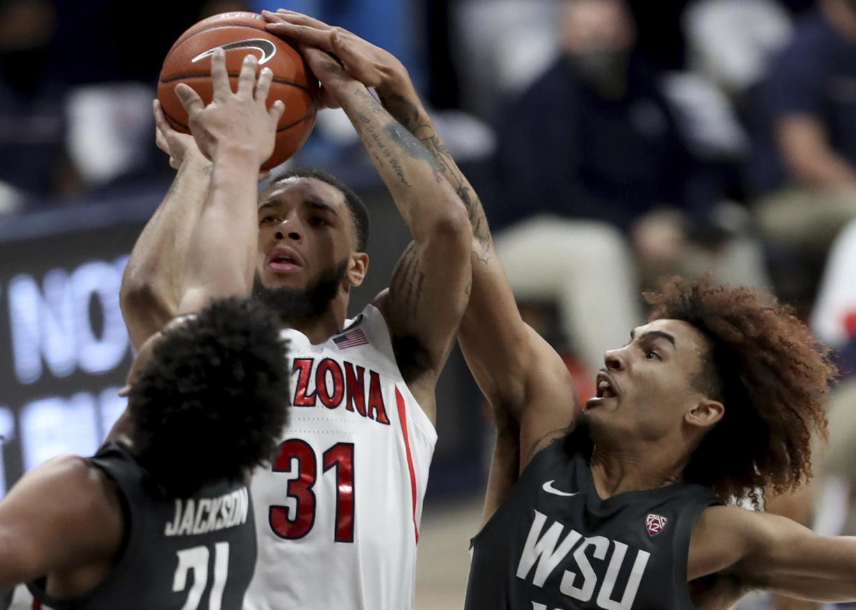 Arizona guard Terrell Brown Jr. (31) gets squeezed into a miss by Washington State center Dishon Jackson (21), left, and guard Isaac Bonton during the first half of an NCAA college basketball game Thursday, Feb. 25, 2021, in Tucson, Ariz.
