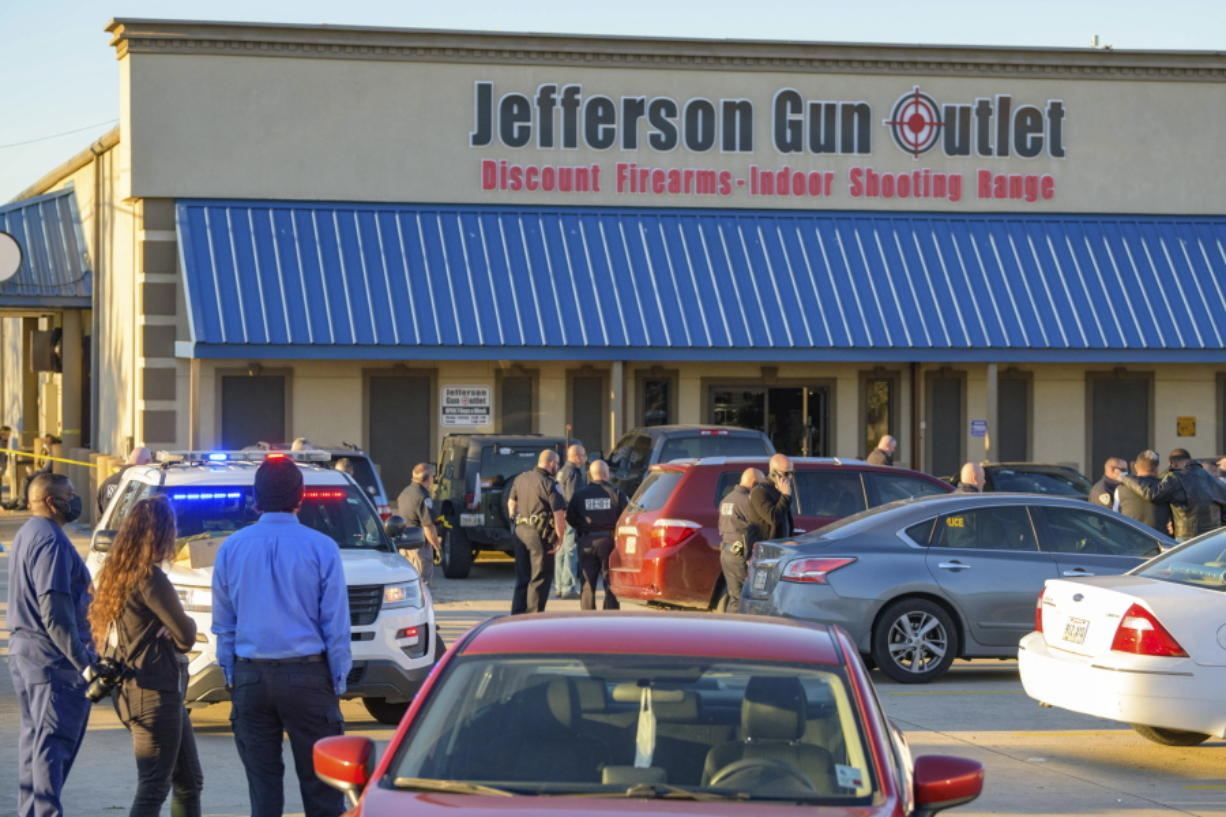 Bystanders react at the scene of a multiple fatality shooting at the Jefferson Gun Outlet in Metairie, La., Saturday, Feb. 20, 2021. A suspect fatally shot two people at a gun store in a suburb of New Orleans on Saturday afternoon, and the shooter also died during gunfire as others engaged the suspect both inside and outside the outlet, authorities said.