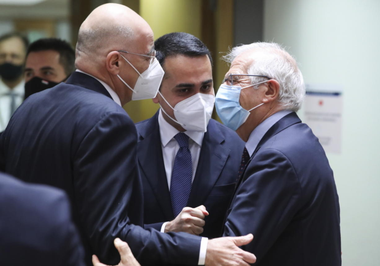 Greek Foreign Minister Nikos Dendias, left, greets Italy's Foreign Minister Luigi Di Maio, center, and European Union foreign policy chief Josep Borrell during a meeting of EU foreign ministers at the European Council building in Brussels, Monday, Feb 22, 2021. European Union foreign ministers on Monday will look at options for imposing fresh sanctions against Russia over the jailing of opposition leader Alexei Navalny as the 27-nation bloc considers the future of its troubled ties with the country.