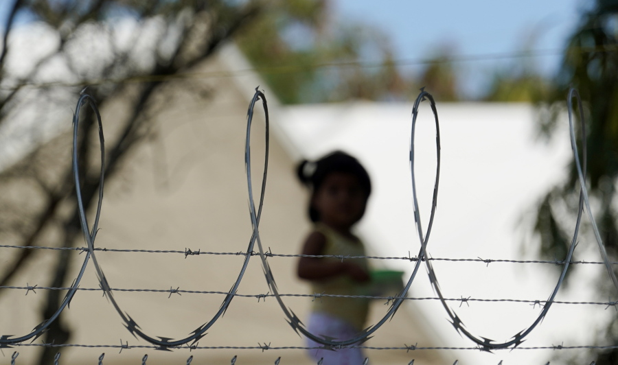 """FILE - In this Nov. 18, 2020, file photo, a child plays at a camp for asylum seekers stuck at America's doorstep, in Matamoros, Mexico. More people have been arriving at an encampment in Matamoros, a dangerous city just south of the Texas border where hundreds of asylum-seekers have been waiting under Trump's """"Remain in Mexico"""" program. It's possible even more may come after the Biden administration announced Friday, Feb. 12, 2021, that it would allow an estimated 25,000 people sent back by the program to enter the U.S. as their cases are reviewed."""
