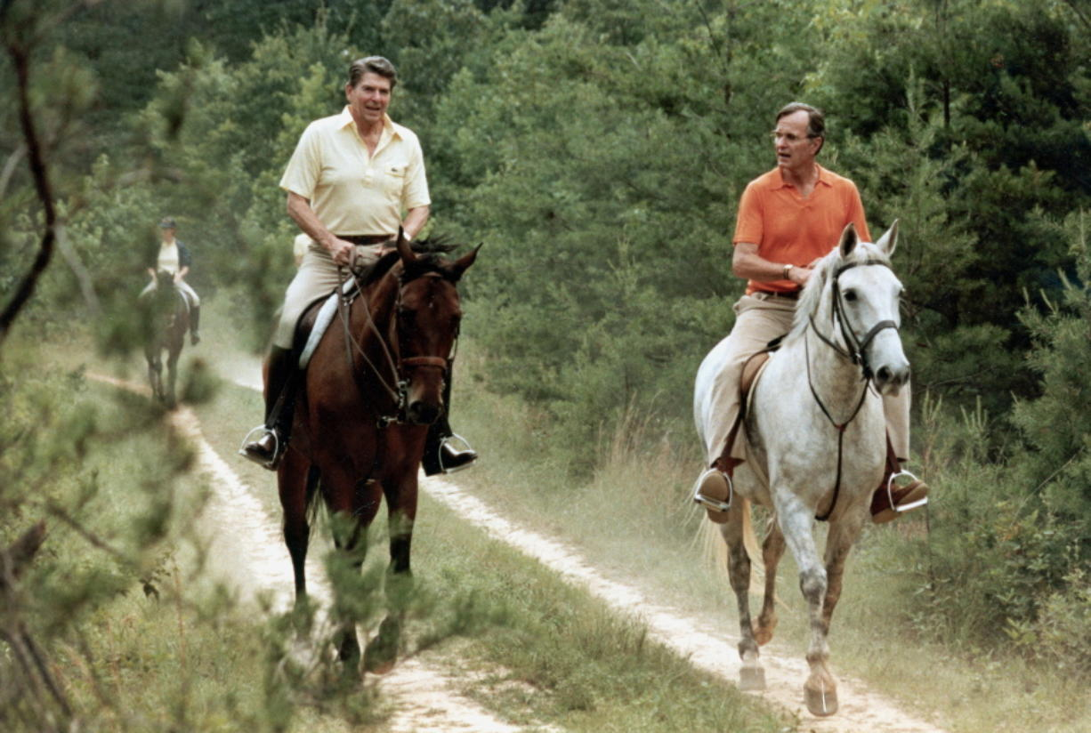 FILE - In this July 1981 file photo released by The White House, U.S. President Ronald Reagan, left, and Vice President George Bush go horseback riding at Camp David, Md. The compound in the Maryland mountains just 60 miles from the capital features everything from a bowling alley to an archery range. It's been used by every president since Franklin Delano Roosevelt first went there in 1943 as a personal hideaway.