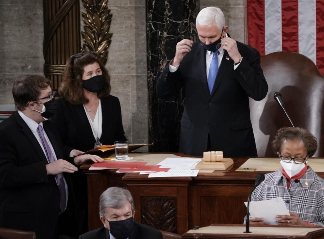 In this Jan. 6, 2021, photo, Senate Parliamentarian Elizabeth MacDonough, left, works beside Vice President Mike Pence during the certification of Electoral College ballots in the presidential election, in the House chamber at the Capitol in Washington. Shortly afterward, the Capitol was stormed by rioters determined to disrupt the certification. MacDonough has guided the Senate through two impeachment trials, vexed Democrats and Republicans alike with parliamentary opinions and helped rescue Electoral College certificates from a pro-Trump mob ransacking the Capitol. (AP Photo/J.