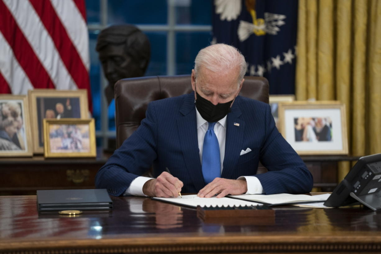 FILE - In this Feb. 2, 2021, file photo, President Joe Biden signs an executive order, in the Oval Office of the White House, in Washington.  Biden is signing an executive order Wednesday to review the United States' supply chains for large capacity batteries, pharmaceuticals, critical minerals and semiconductors.